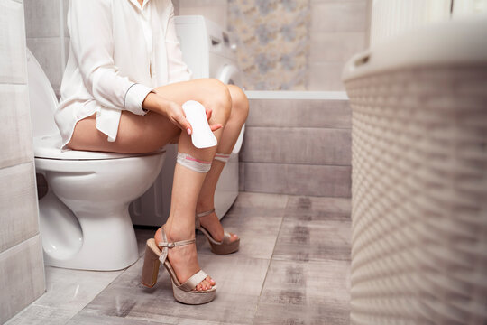 Female hygiene products concept, woman sitting on toiled and holding clean pad