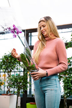 Beautiful, charismatic  girl florist holding orchid flower in her hands and smiling.