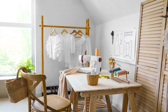 Table with sewing machine and tailor's supplies in atelier