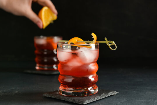 Woman squeezing fresh orange in glass with tasty Negroni cocktail on dark background