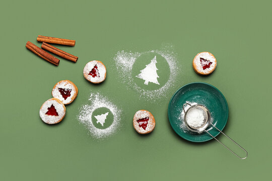 Tasty Linzer cookies with icing sugar on color background