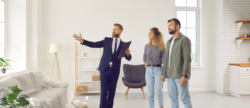Realtor giving future tenants or first time buyers tour about modern apartment. Boyfriend and girlfriend or husband and wife planning to buy new home and meeting with real estate agent in new house