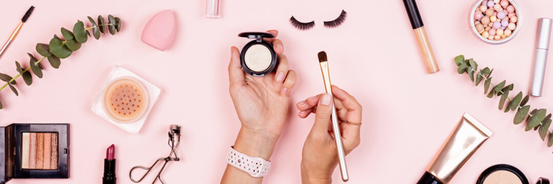 Flat lay of professional Cosmetics set on pastel pink background. Woman holding hands makeup brush