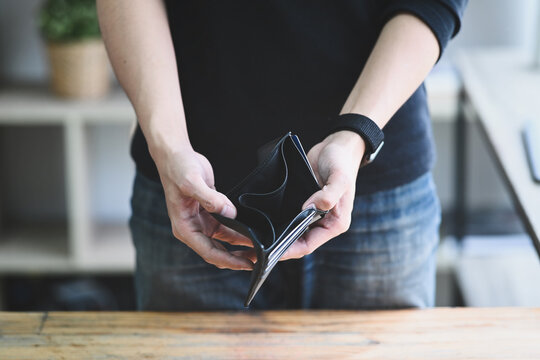 Man holding empty wallet. Bankruptcy, unemployment and financial crisis concept.