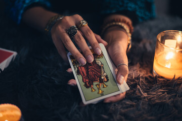 Obraz Fortune teller holding tarot cards deck. tarot cards and burning candles. Astrologists and forecasting concept. - fototapety do salonu