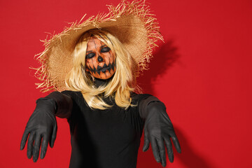 Young woman with Halloween makeup mask wearing straw hat black scarecrow costume raise hands close eyes like dead isolated on plain red background studio portrait. Celebration holiday party concept.