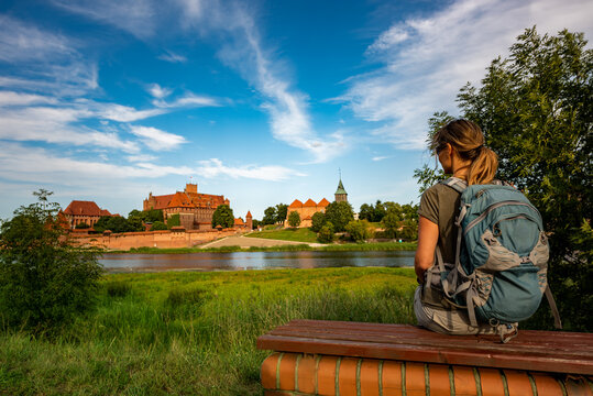 Tourist Backpacker woman enjoys the view of Malbork Castle