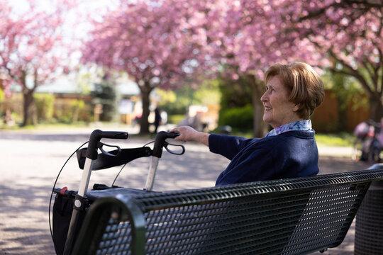 Seniorin sitzt allein im Park im Frühling auf einer Bank , den Rollator neben sich