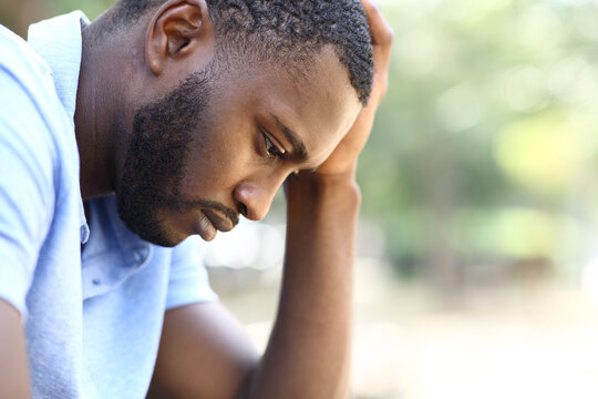 Worried black man complaining alone in a park
