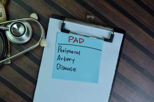 PAD - Peripheral Artery Disease write on sticky notes isolated on Wooden Table.