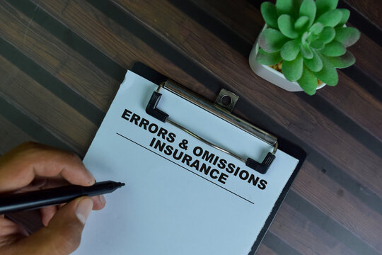 Errors & Omissions Insurance write on a paperwork isolated on Wooden Table.