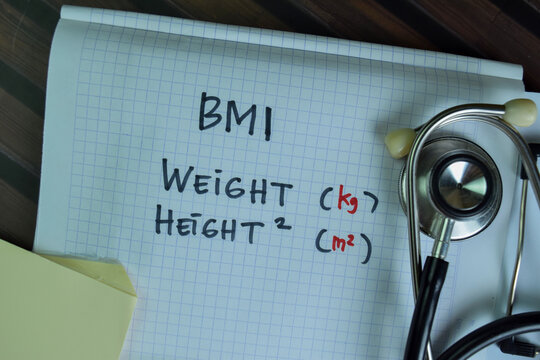 BMI - Weight and Height write on a book isolated on Wooden Table.