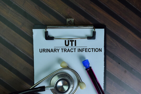 UTI - Urinary Tract Infection write on a paperwork isolated on Wooden Table.