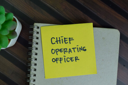 Chief Operating Officer write on sticky notes isolated on Wooden Table.