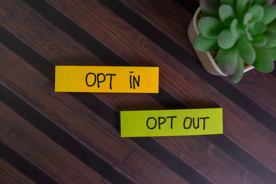 Opt In and Opt Out write on sticky notes isolated on Wooden Table.