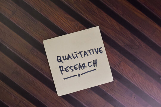 Qualitive Research write on sticky notes isolated on Wooden Table.