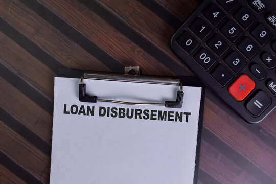 Loan Disbursement write on a paperwork isolated on Wooden Table.