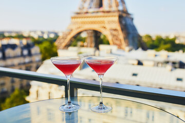 Fototapeta Two Cosmopolitan cocktails in traditional martini glasses with view to the Eiffel tower, Paris, France obraz