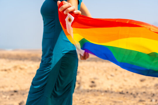 Lgbt symbol, an unrecognizable lesbian person in a green dress and a white hat with the rainbow flag by the sea