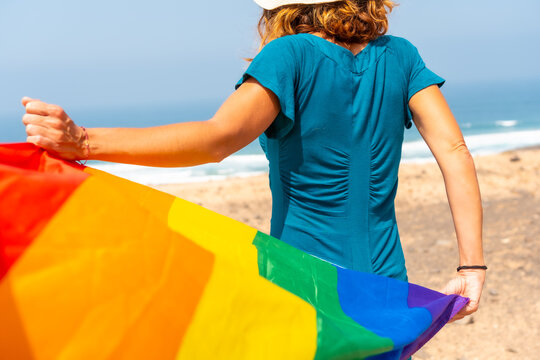 Lgbt symbol, an unrecognizable lesbian person from behind waving the flag by the sea