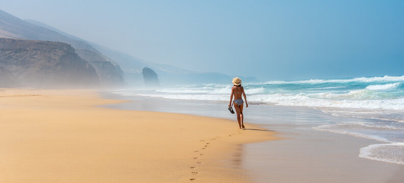Panoramic of a young tourist with a hat walking alone on the Cofete beach of the Jandia natural park, Barlovento, south of Fuerteventura, Canary Islands. Spain