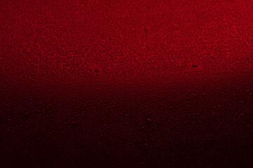 Fototapeta Water drops on black glass. Background illuminated with red light. obraz