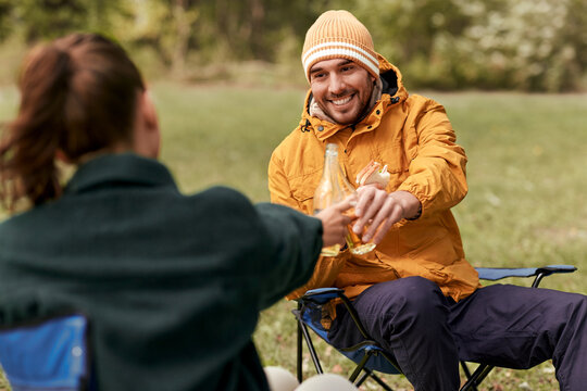 camping, tourism and travel concept - happy couple drinking beer and eating sandwiches at tent camp