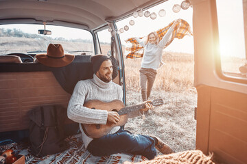 Obraz Handsome young man playing guitar for his girlfriend while spending time in motor home - fototapety do salonu