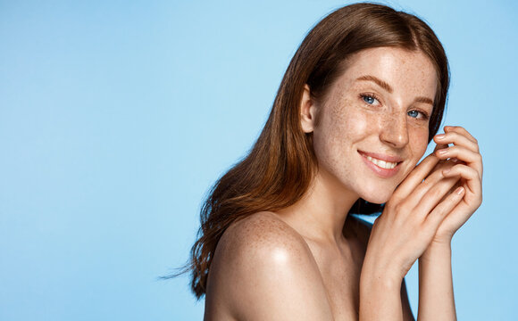 Beautiful female model gazing at camera, smiling with white teeth, head and shoulder portrait with clean body, standing over blue background