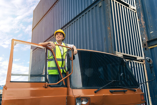 Asian woman truck driver wear yellow helmet and safety vest standing in front of truck vehicles.