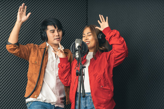 Asian couple singers in a recording studio using a studio microphone with passion in music recording studio