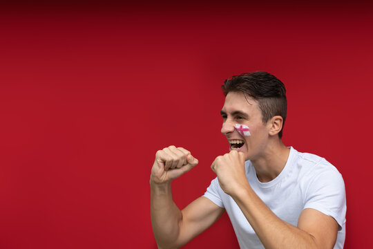 English football fan happy for his national team, isolated on red background. Copy space and flag painted over face