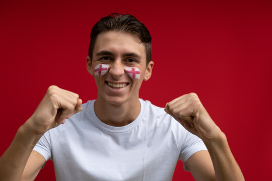 English football fan happy for his national team, isolated on red background. Flag painted over face