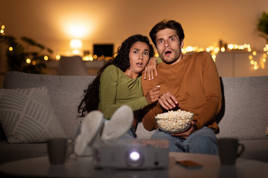 Scared Couple Watching Horror Movie In Shock Using Projector Indoors