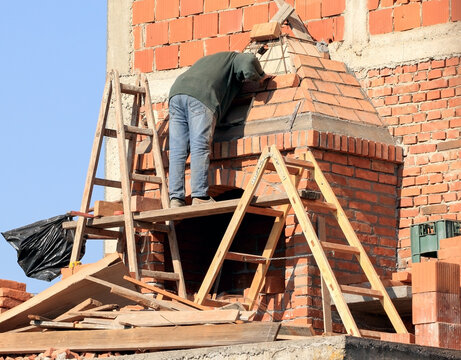An experienced ladder worker monitors the interior  works of the chimney