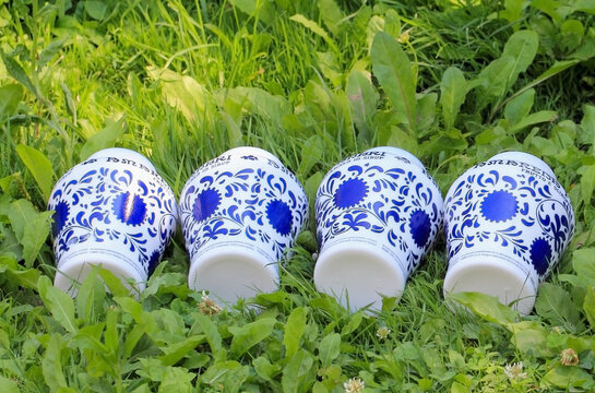 Four ceramic vases of blue and white combination laid on the grass