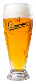 uzhgorod, ukraine - SEP 02, 2015: glass of beer with staropramen label. yellow alcohol drink with foam. popular czech refreshment beverage isolated on a white background