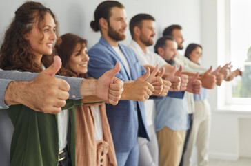 Fototapeta Group of successful business people doing like gesture all together. Team of ambitious confident young, mature and senior businesspeople standing in modern office, giving thumbs up and smiling obraz