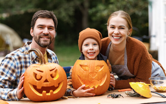 Happy family parents and little boy son carving pumpkins in backyard