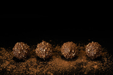 Chocolate ball candy with nuts on dark background with cocoa powder. Horizontal with copy space