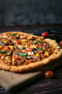 Fresh baked thin crust Italian pizza with tomato sauce pepper cheese and basil leaf on Dark rustic table background.