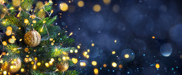 Obraz Christmas Tree In Blue Night - Golden Balls On Fir Branches With Defocused Lights In Abstract Background - fototapety do salonu