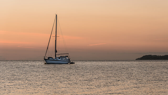 a sailboat is at anchor at sunset and a man is standing in a window in the stern
