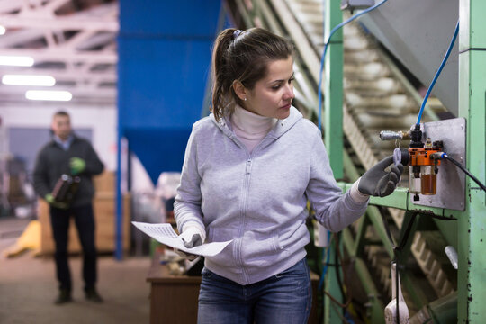 Focused woman supervising sensors of machine of olive oil cold pressing on family artisanal factory