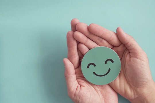 Hands holding green happy smile face paper cut, good feedback rating,positive customer review, experience, satisfaction survey ,mental health assessment, child wellness,world mental health day concept