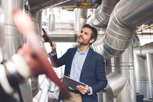 Businessman holding digital tablet while checking machinery at industry