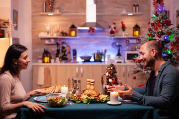 Obraz Happy family sitting at romantic dining table in xmas decorated kitchen enjoying christmas dinner together. Cheerful people enjoying winter holiday season celebrating christmastime - fototapety do salonu