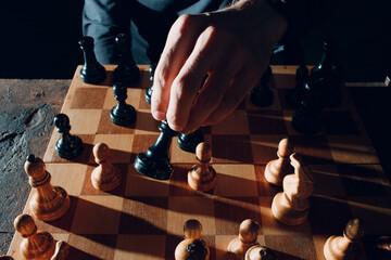 Fototapeta premium Young adult man play chess in dark