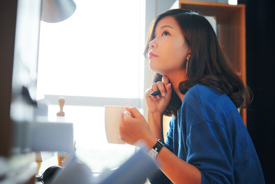 Pensive young Asian designer in blue sweater holding pen and looking at monitor while drinking coffee in office