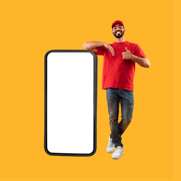 Middle-Eastern Guy Standing Near Big Smartphone Gesturing Thumbs-Up, Yellow Background